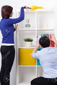 dusting furniture. Daughter And Her Mother During Dusting Furniture Stock Photo - 27087314 M