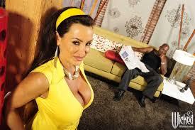 Lisa Ann titty fucks and licks a dark cock in a yellow dress.