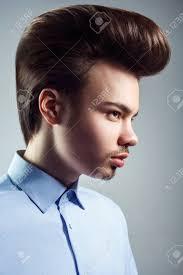 レトロな古典的なポンパドール髪型と若い男の側面図ですスタジオ撮影し