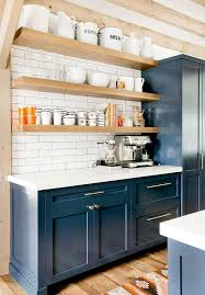 navy blue shaker cabinets with blond floating shelves