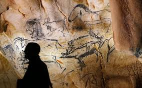 a visitor looks at cave art depicting animals in the caverne du pont d