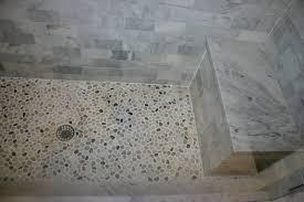 pebble tile shower floor including white marble tile shower walls