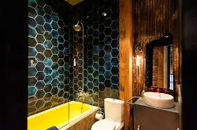 view in gallery stunning eclectic industrial bathroom with bold hexagonal tiles and a bathtub in yellow design