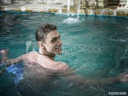 man look back ward while swimming in the pool