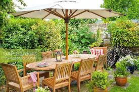outdoor dining area in secluded corner of family garden with wooden table chairs and parasol