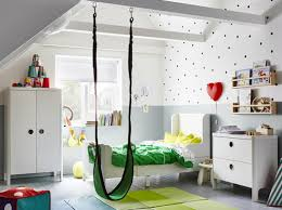 A children's bedroom furnished with a white extendable bed, a wardrobe and  a chest of