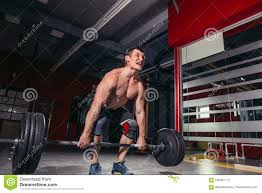 young man lifting barbells during deadlift workout