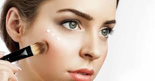 woman with healthy skin applying cream highlighter under eye