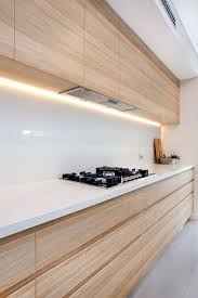 light colored wooden cabinets with a white backsplash and countertops look very chic