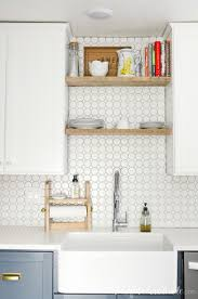 large farmhouse sink in a kitchen with open shelving above the sink and white octagon tile