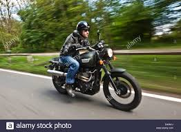 man in black leathers on triumph scrambler motorbike london stock
