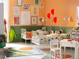 Children's bedroom with two white, extendable beds, writing table and  chair. Walls painted