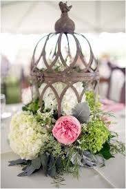 Pillar candles, crystal clear candelabras, and birdcageseach centerpiece  is easily the center of attention.