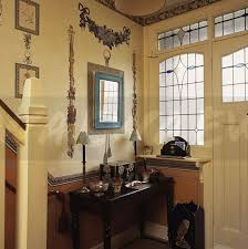 decoupage garlands on wall above console table in small neutral hall with stained glass window above beside door