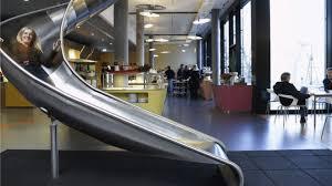 future office design. woman on the google slide at its zurich hq future office design
