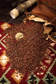 spilled coffee beans and african medallion with eagle stock photo