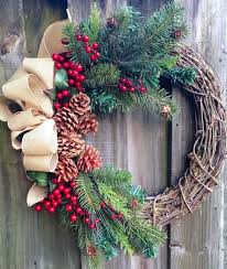 Winter wreath or Christmas wreath using grapevine, red berries, pine, and  pine cones