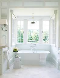a roll top freestanding bathtub sits on marble staggered floor tiles in a windowed nook illuminated by a paris flea market chandelier