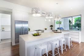 modern white kitchen with silver drum pendant lights