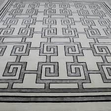 black and white geometric rug. add a classic touch to your space with caesar, white geometric rug made from black and