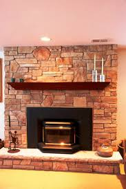 plain living room decorating idea with natural stone fireplace along with black