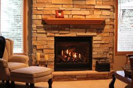 a fireplace with natural stone wall system and wood shelf over the firebox a cozy corner