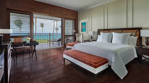 luxury beachfront ocean room bed padded bench desk by patio window wood shutters
