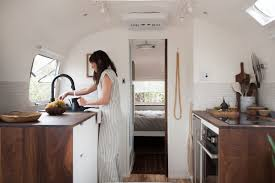 kate works in her airstream s new kitchen featuring custom built walnut counters and painted