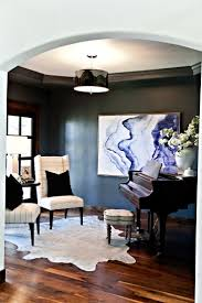 Formal sitting room with metallic cowhide rug, navy walls, grand piano and  abstract indigo