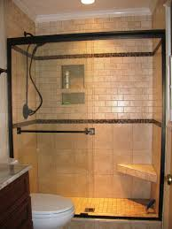 interior black shower on beige tile wall connected by beige corner shelf and glass sliding