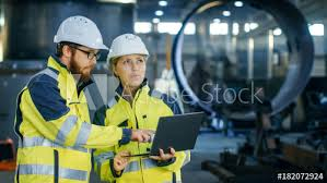 Male And Female Industrial Engineers In Hard Hats Discuss New