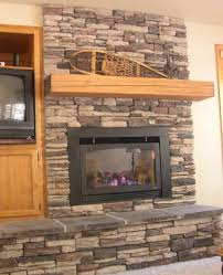 interior grey stack stone fireplace with brown wooden mantel shelf and rectangle black metal firebox