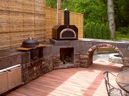 Beautiful outdoor kitchen with the Mario Batali Etna Grande wood fired pizza  oven as the main