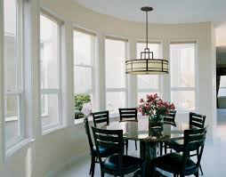 dining room cream drum pendant lamp over black wooden dining set connected by cream wall