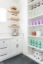 a gray slate floor contrasts a white kitchen pantry boasting white shaker cabinets adorned with oil rubbed bronze pulls and statuary quartz countertop fixed
