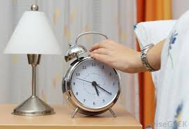 a mechanical alarm clock has bells on top of the clock face that are struck with a mechanical hammer when the correct hour has arrived