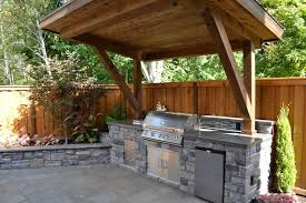 Rustic Patio with Polished concrete, Outdoor kitchen, Raised beds, Stacked  stone, Fence
