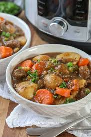 two bowls filled with instant pot beef stew topped with fresh parsley
