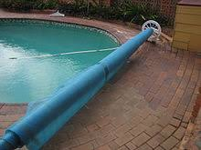 a rolled up thermal bubble pool cover used to reduce water loss from evaporation and heat loss from the pool