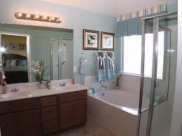 brown wooden bathroom vanity with white top and large mirror on blue