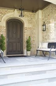 magnificent door knocker in entry traditional with double barn door hardware next to wood front door alongside entry bench and brick color
