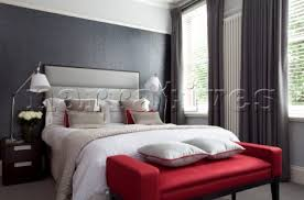 Muted grey bedroom with red footstool and matching anglepoise bedside lamps  in contemporary London h
