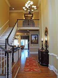 this neutral two story foyer shows off the staircase hardwood flooring and a chandelier landscape art on both levels ties the two spaces together