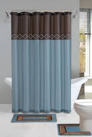 blue and brown shower curtain with blue rug and toilet and grey color walls