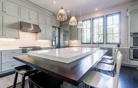 kitchen with quartz countertops and wood breakfast bar with industrial style pendant lights