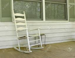 white wooden rocking chair. An Old White Painted Wooden Rocking Chair Sitting Outside On A Dirty Front Porch Stock Photo O