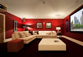 this bright red media room has a light cream sectional sofa and an ottoman coffee table that contrast beautifully with the bold choice of paint color