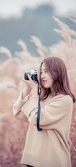 Asian girl use camera, reeds 1242x2688 ...