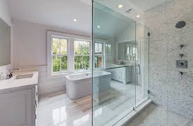 master bathroom with large clear glass shower door with white mosaic tile and dual vanities