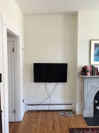 so we hung the tv in the corner which as you can see left us with a mess of cables running down the wall there are various cord managers that can be